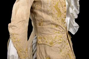 White linen coat belonging to William Prescott having collarless, with silk crewel embroidery in shades of yellow and gold.